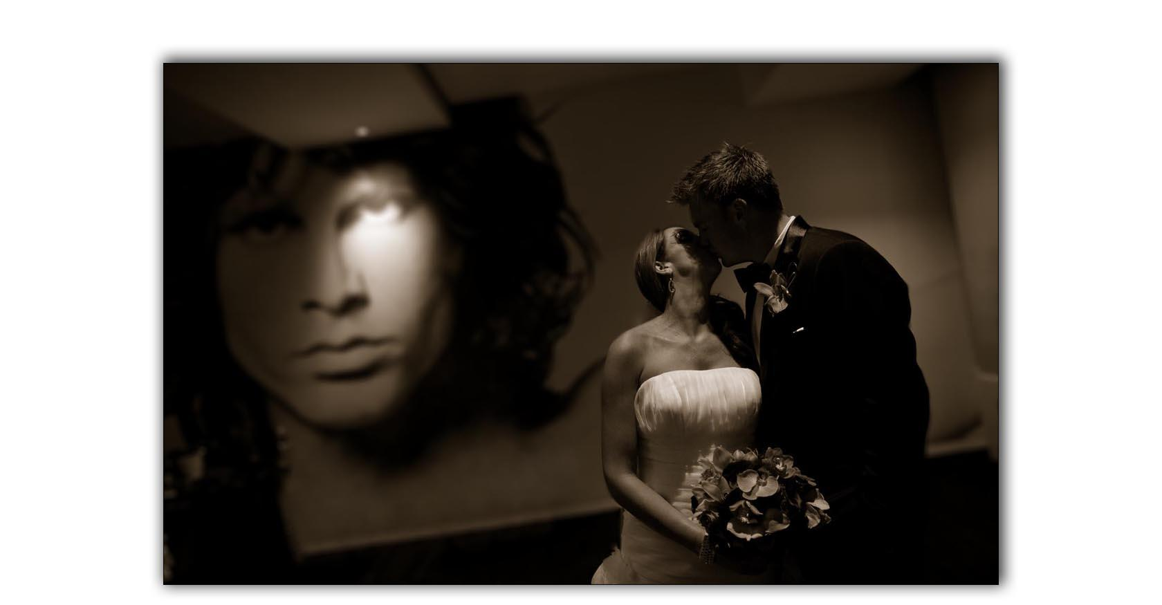 Hard Rock San Diego bride and groom wedding kiss, under Jim Morrison's gaze